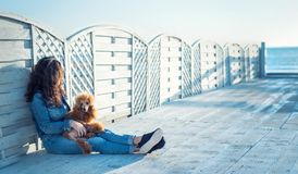 Woman with her dog at wooden terrace on the sea beach . Stock Images