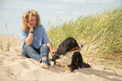Woman with her dogs. Mature woman with her dog on sand and grass sitting Royalty Free Stock Image