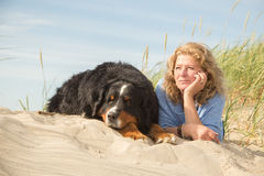 Woman with her dogs. Mature woman with her dog on sand and grass sitting Stock Images