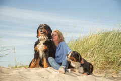 Woman with her dogs. Mature woman with her dogs on sand and grass sitting Stock Images