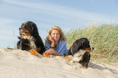 Woman with her dogs. Mature woman with her dogs on sand and grass sitting Stock Photos