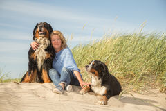 Woman with her dogs. Mature woman with her dogs on sand and grass sitting Royalty Free Stock Photo