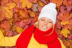 Woman with her eyes closed laying in leafs Stock Image