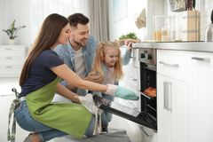 Woman and her family taking out tray with baked buns from oven royalty free stock images
