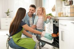 Woman and her family taking out tray with baked buns from oven stock photo