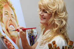 Woman in her fifties painting a portrait Stock Photography
