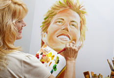 Woman in her fifties painting a portrait Royalty Free Stock Photography
