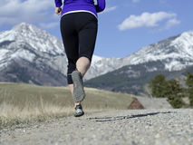 Woman in her fifties running in Montana. A woman in her fifties running down a dirt road under a beautiful blue sky with the mountains in the background Stock Photography