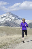 Woman in her fifties running in Montana Stock Images