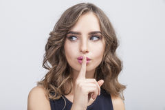 Woman with her finger near pink lips Stock Image