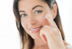 Woman in her forties applying  face cream Royalty Free Stock Image