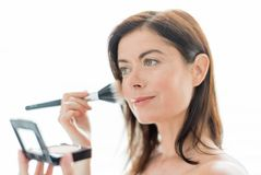 Woman in her forties applying makeup Stock Image