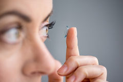 Woman in her forties inserting contact lenses Royalty Free Stock Image