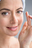Woman in her forties inserting contact lenses Royalty Free Stock Images