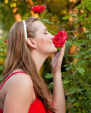 Woman in her garden sniffing at the roses Stock Images