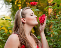 Woman in her garden sniffing at the roses Royalty Free Stock Image