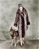 Woman in her Giraffe patterned fur coat and her dog Stock Photo