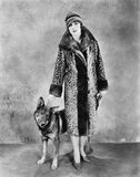 Woman in her Giraffe patterned fur coat and her dog Royalty Free Stock Photo