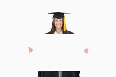 A woman in her graduation gown holds a blank sheet in front of h Stock Images