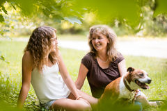 Woman with her grownup daughter and dog, outdoors. Stock Photos