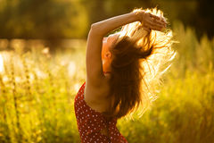 Woman with her hair in the evening sun Stock Images