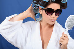 Woman with her hair in rollers. Holding a brush and wearing sunglasses Royalty Free Stock Photos