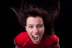 Woman with her hair in wind,screaming in fury. Beautiful young woman with her hair in the wind, screaming in fury, isolated on black background stock images