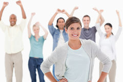 Woman with her hands on hips with people behind raising their ar Royalty Free Stock Photos