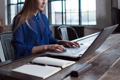 Woman with her hands on laptop keyboard. Designer sitting at worktable with notebook and computer on it. Royalty Free Stock Photo
