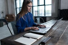 Woman with her hands on laptop keyboard. Designer sitting at worktable with notebook and computer on it. Royalty Free Stock Photos