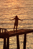 Woman with her hands up watching the sun set Stock Photography