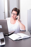 Woman in her homeoffice on the phone.  Royalty Free Stock Photo