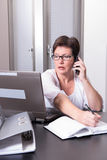 Woman in her homeoffice on the phone.  Stock Photo