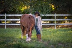 Quiet Moments. Woman and her horse in a pasture royalty free stock photos