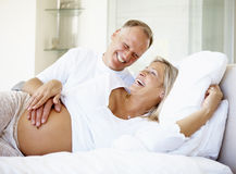 Woman with her husband relaxing on bed Royalty Free Stock Photo