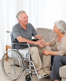 Woman with her husband in a wheelchair. Women with her husband in a wheelchair at home Royalty Free Stock Photo
