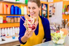 Woman in her ice cream parlor presenting her newest sundae creation. Woman in ice cream parlor presenting her newest sundae creation, looking into the camera stock images