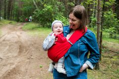 Happy woman with infant baby in forest having fun. Woman and her infant baby outdoors with Baby carrier slings Stock Photo