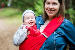 Happy woman with infant baby in forest having fun. Woman and her infant baby outdoors with Baby carrier slings Stock Photography