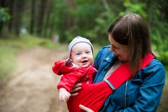 Woman and her infant baby outdoors. With Baby carrier slings Royalty Free Stock Photography