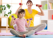 Woman and her kid daughter doing fitness exercises with dumbbells Royalty Free Stock Images