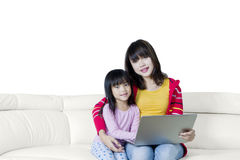 Woman and her kid with laptop on sofa Stock Photography