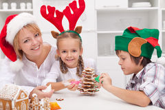 Woman and her kids decorating christmas cookies. Woman with santa hat and her kids dressed as reindeer and elf decorating christmas cookies Stock Photography