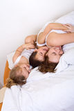 Woman and her kids having fun in a lazy morning. Woman and her kids having fun on the bed in a lazy morning Royalty Free Stock Photography