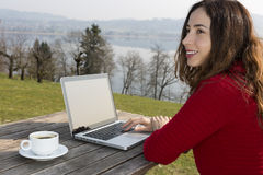 Woman with her laptop and a cup of coffee at a restaurant Stock Images