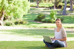 Woman with her laptop sitting in the park Stock Images