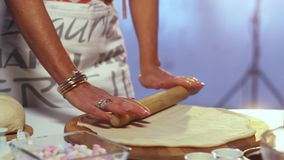 Dough is being rolled out on big round shaped wooden board with rolling pin. Woman in her late 40s wearing white and grey apron is rolling out dough on large stock video