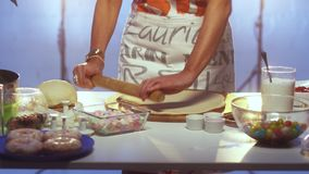 Dough is getting rolled out on big round shaped wooden board with rolling pin. Woman in her late 40s wearing white and grey apron is rolling out dough on large stock video