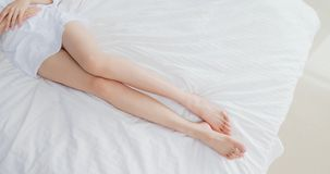 Woman with her leg. Beauty woman lying on the bed with leg stock photography