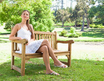 Woman with her legs crossed sitting on a bench Royalty Free Stock Photo
